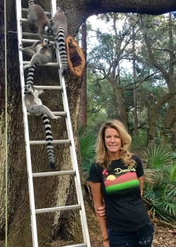 Elizabeth Moore standing in front of a tree with ring-tailed lemurs